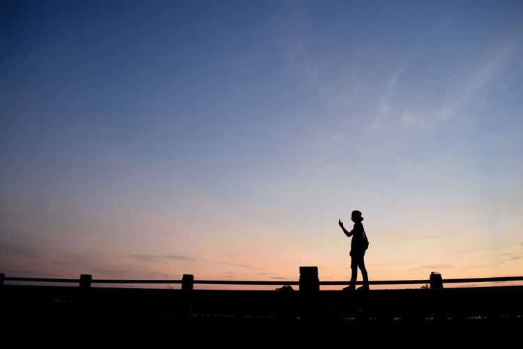 Silhouette Man Standing Against Sky During Sunset