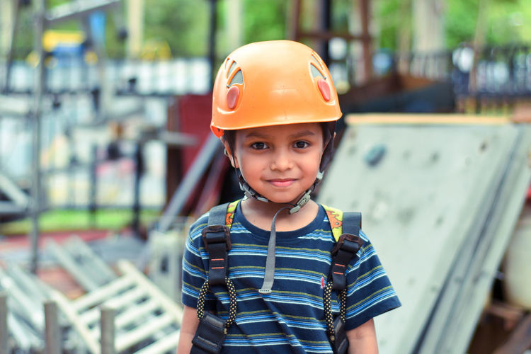 Portrait of little boy wearing helmet and harness