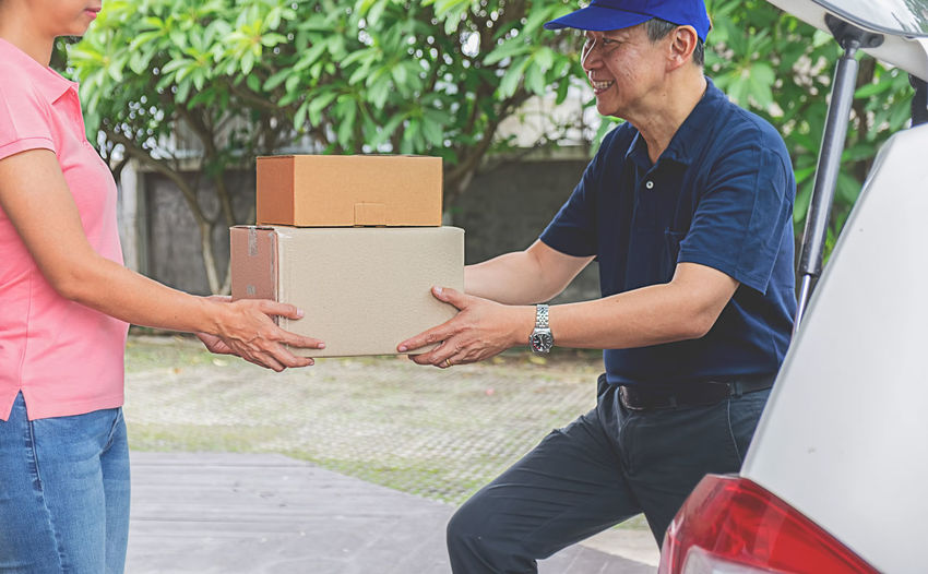 Adult Box Box - Container Cardboard Cardboard Box Casual Clothing Couple - Relationship Day Emotion Holding Land Vehicle Men Midsection Outdoors People Real People Standing Three Quarter Length Togetherness Transportation Two People