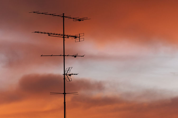 Low angle view of silhouette communications tower against dramatic sky