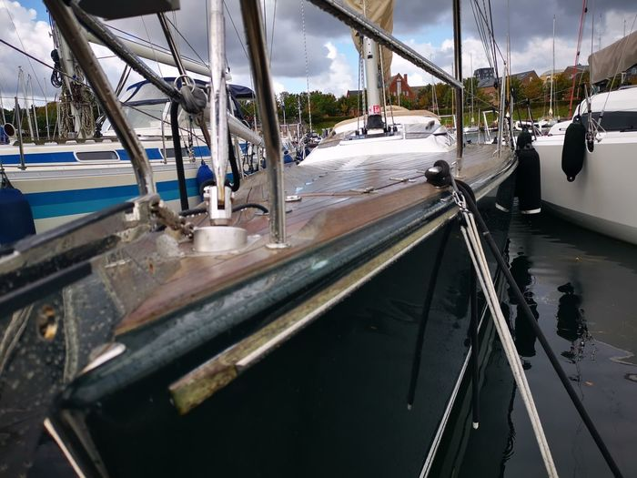 Boats moored on road against sky