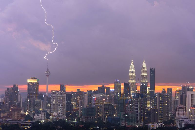 Dramatic sunset with lightning strikes on Kuala Lumpur Tower Building Kuala Lumpur City Center Tourist Attraction  Travel Destinations Architecture Built Structure Building Exterior Sky City Skyscraper Office Building Exterior Cloud - Sky Tower Building Cityscape Tall - High Urban Skyline Storm Lightning Night Illuminated Nature Landscape No People