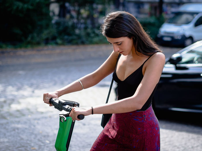 Young woman riding bicycle on road in city