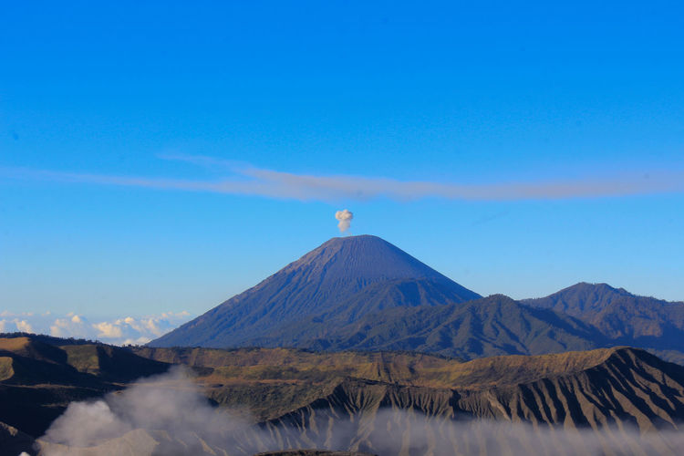 Scenic view of volcano against blue sky