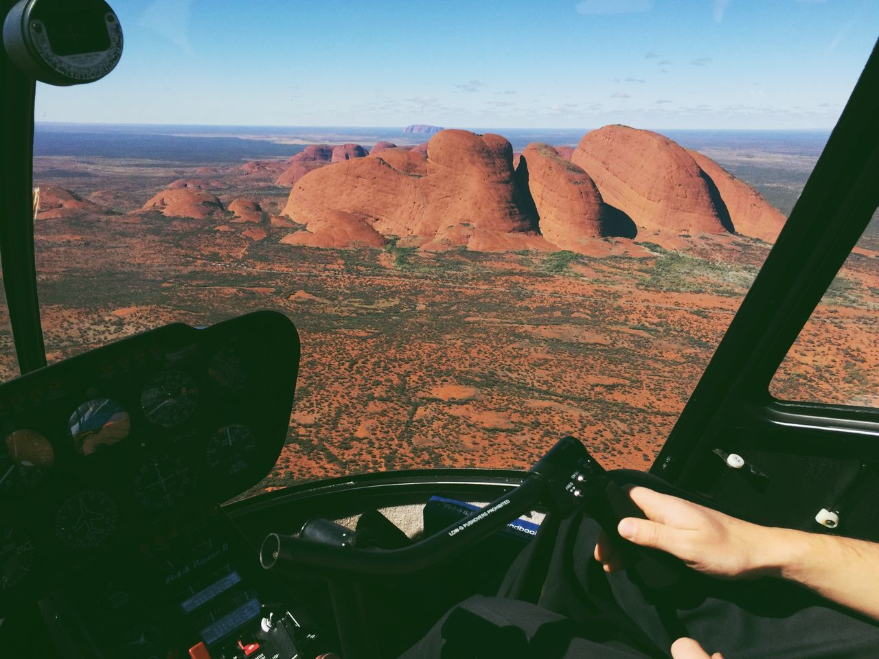 Midsection of pilot flying helicopter by kata tjuta against sky