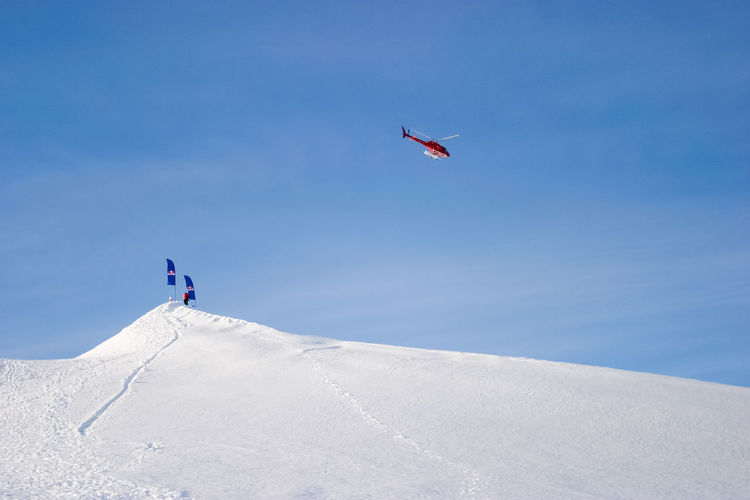 Helicopter flying over snow covered mountain with flags on summit below Adventure Blue Clear Sky Cold Temperature Day Flags Flying Freedom Helicopter Leisure Activity Mid-air Mountain Sky Snow Sport Summit Transportation Travel Winter