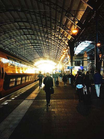 People walking on railroad station platform at night