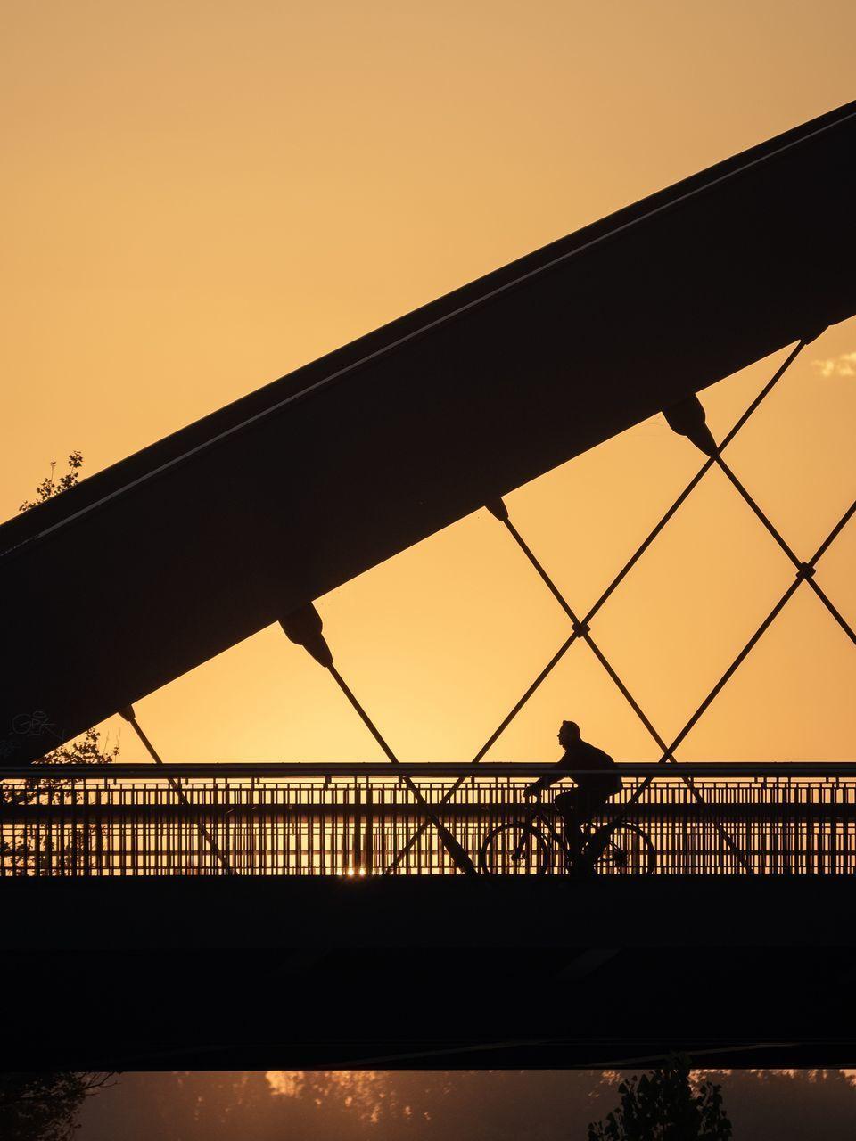 SILHOUETTE MAN BRIDGE AGAINST SKY DURING SUNSET