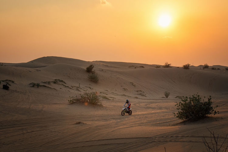 People riding motorcycle on desert against sky during sunset