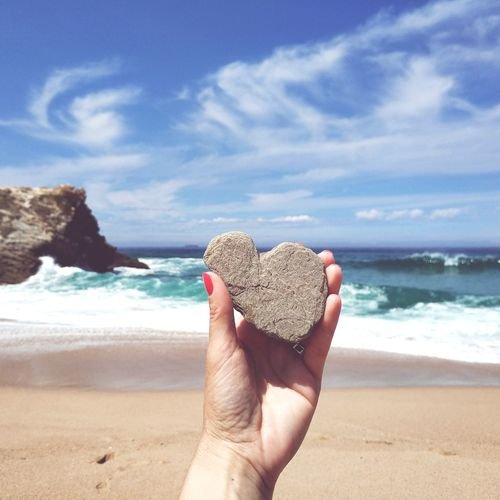 Cropped hand of woman holding heart shape rock at beach during summer