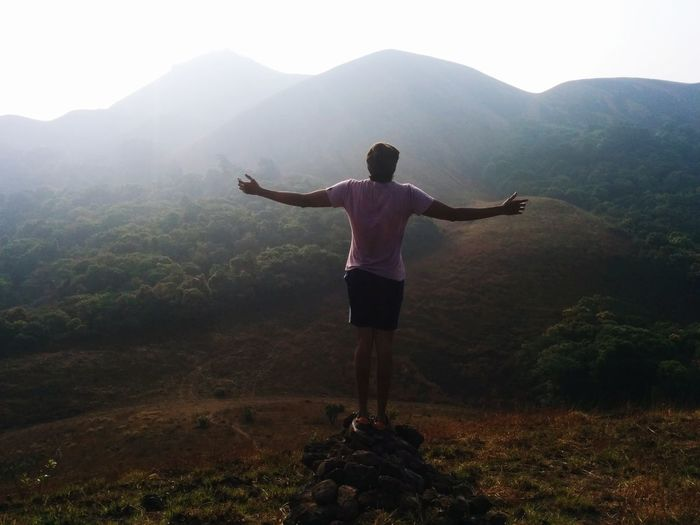 Rear view of man with arms outstretched standing on mountain