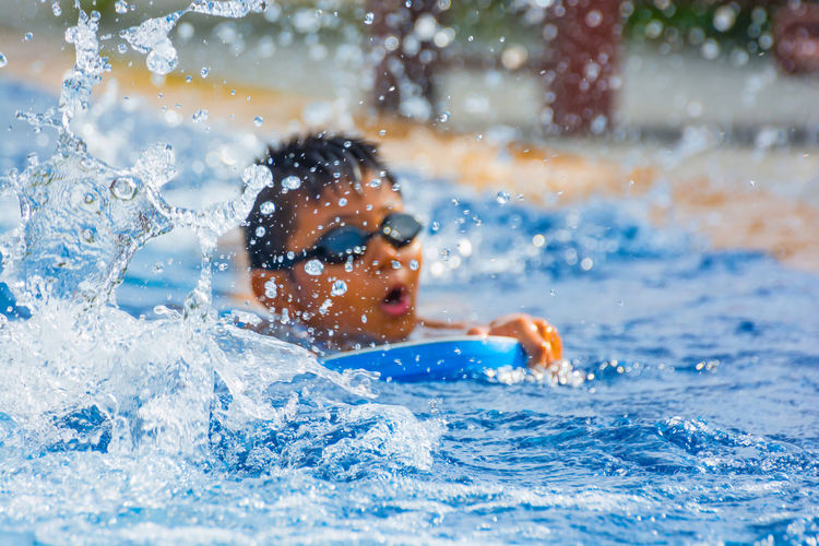ASIAN BOY CARRYING FOAM PAD DURING LEARNING SWIMMING Exercise Day Focus On Foreground Healthy Leisure Activity Lifestyles Motion One Person People Practicing Real People Splashing Swim Swimming Pool Training Water Waterfront