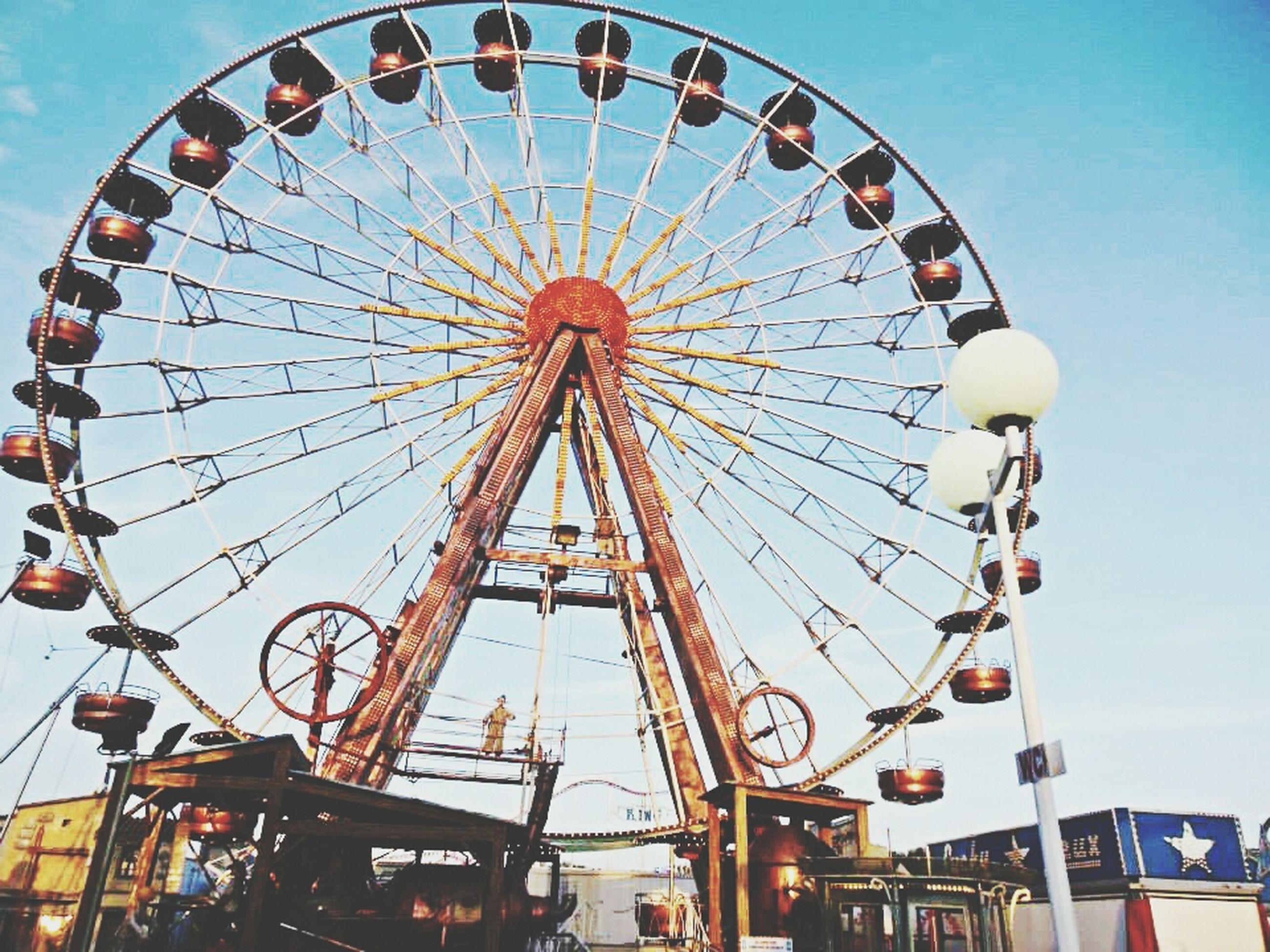 amusement park, amusement park ride, ferris wheel, arts culture and entertainment, low angle view, sky, fun, enjoyment, built structure, multi colored, fairground ride, leisure activity, day, outdoors, architecture, metal, chain swing ride, blue, fairground, large