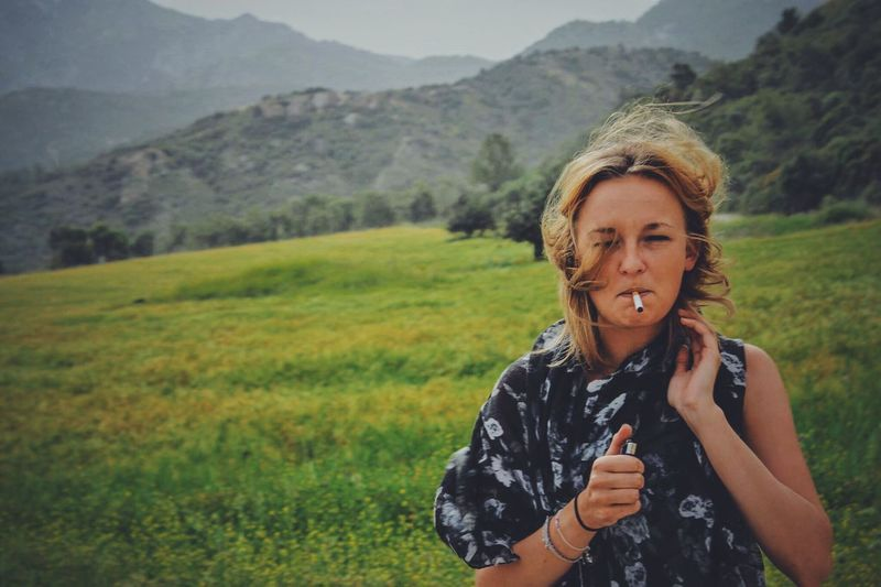 Portrait Of Young Woman Smoking In Mountains