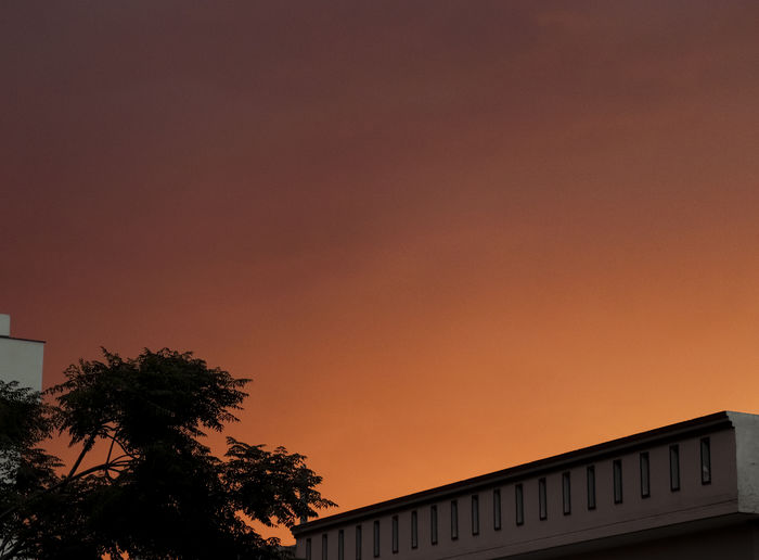 Low angle view of building against orange sky