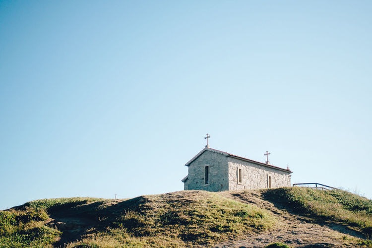 Low angle view of chapel on hill against sky