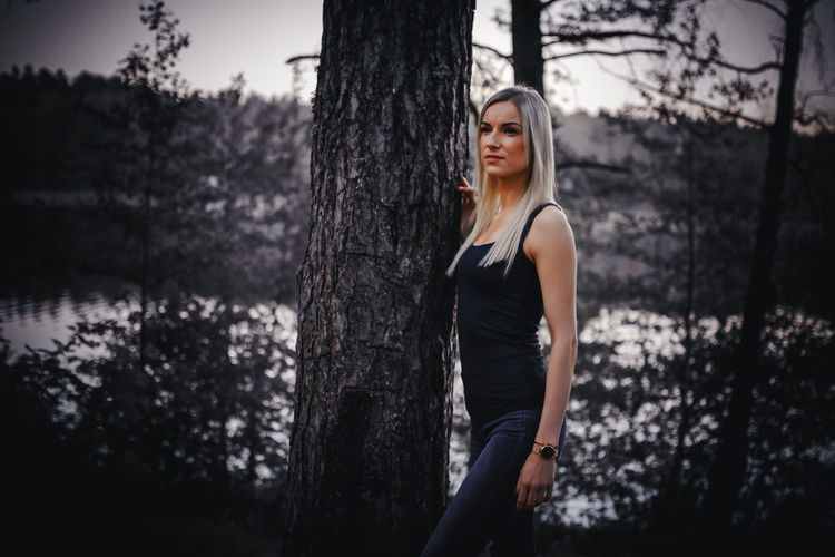 Mid adult woman looking away while standing by tree trunk in forest