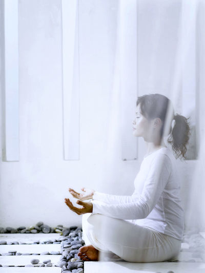 Young Woman Meditating In Balcony