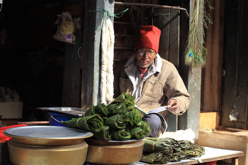 Bagdhapur, Nepal Casual Clothing Food Freshness Leisure Activity Lifestyles Looking At Camera Looking In Your Eyes Market Market Place Market Stall Nepali  Nepali People Newspaper Peaceful Portrait Reading Newspaper Sitting Fine Art Photography On The Way