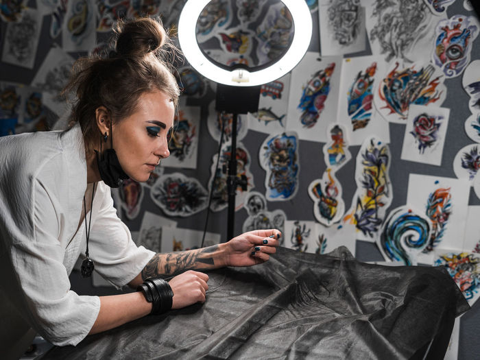 Piercing master, portrait One Person Real People Indoors  Sitting Casual Clothing Holding Art And Craft Creativity Small Business Young Adult Adult Occupation Skill  Lifestyles Fashion Women Working Craft Design Professional Tailor Hairstyle