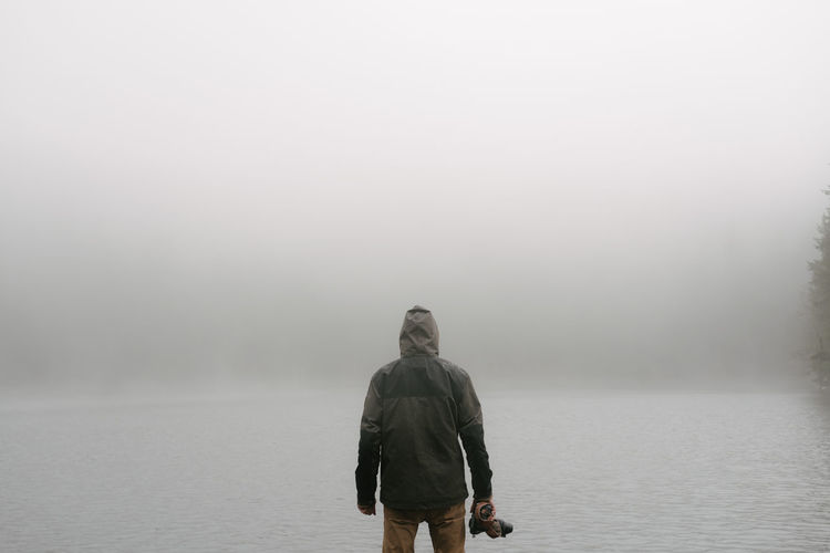 Rear View Of Man Standing In Front Of Lake In Foggy Weather