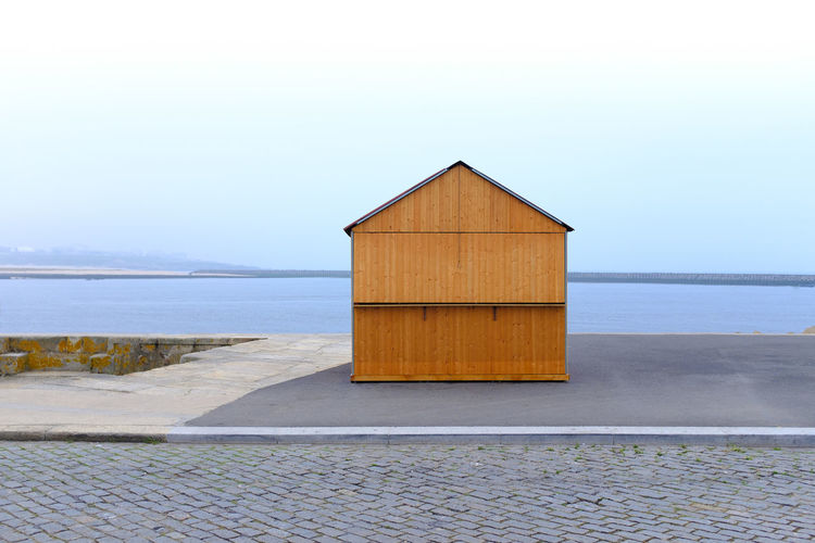 Beach hut by sea against clear sky