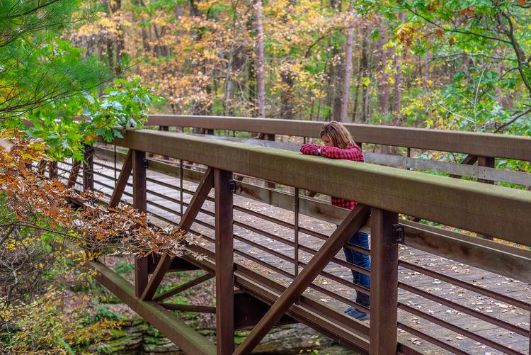Woman sitting on bench by footbridge