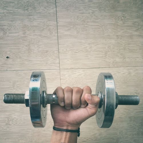 Cropped Hand Lifting Dumbbell On Floor