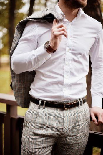 Midsection of businessman wearing suit in forest