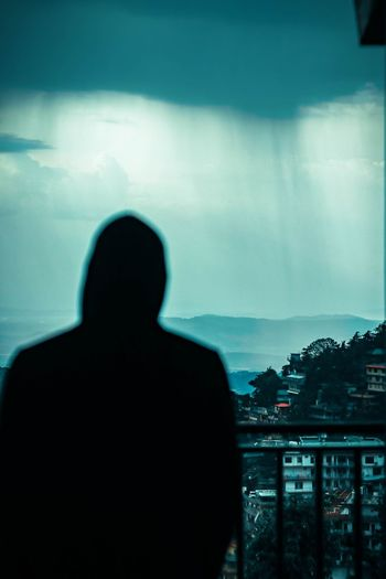 Rear view of silhouette man looking at cityscape against sky