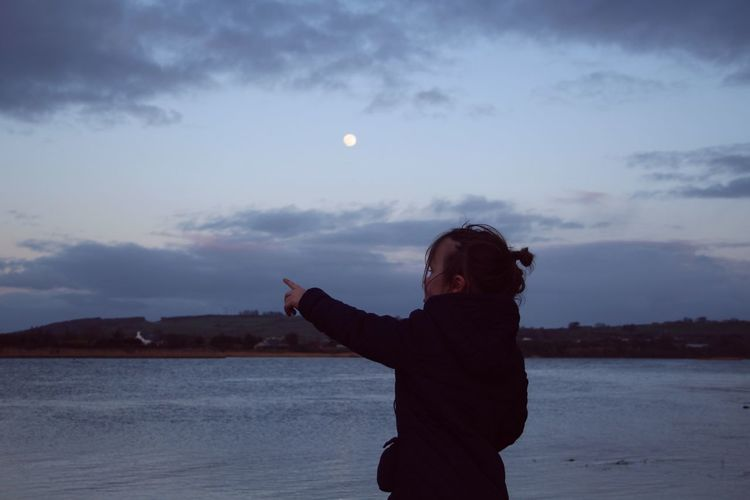 Girl pointing while standing at beach