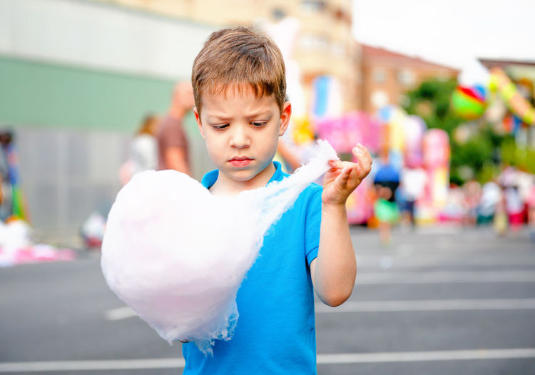 Kid eating cotton candy in a summer festival Vacation Urban Colorful City Holiday Street Youth Little Adorable Hand People Casual One Happiness Cute Joy Enjoy Leisure Outside Lifestyle Cheerful Summer Caucasian Outdoor Fairground Recreation  Motion Portrait Entertainment Amusement  Carnival Park Fun Childhood Happy Sugar Food Sweet Eat Festival Fair Child Kid Cotton Candy Cotton Candy