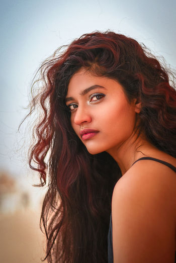 Portrait of beautiful young woman with wavy hair against sky