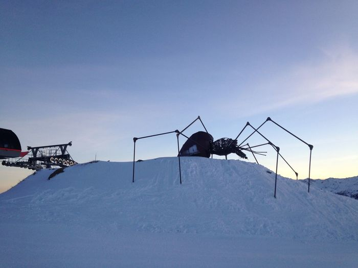 Ski lift on field by snowcapped mountain against sky