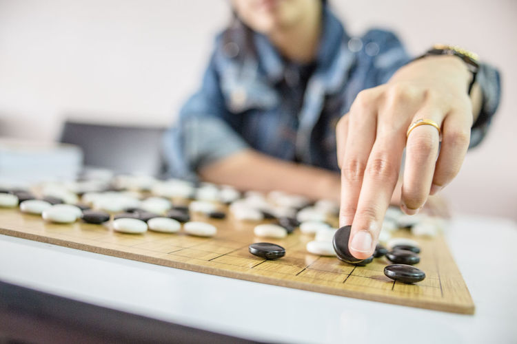 Midsection of man playing board game on table
