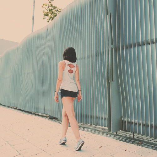 Rear view of mid adult woman walking on footpath against fence