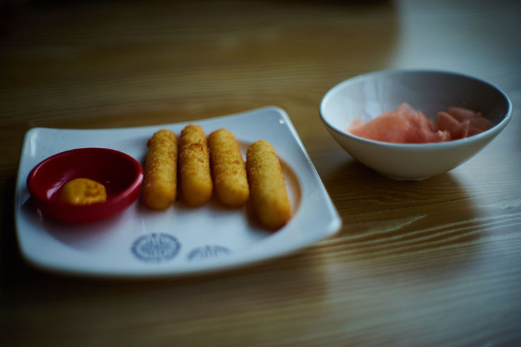 Cheese sticks in plate on table