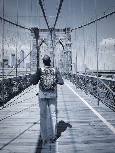 Rear view of man standing on brooklyn bridge against sky