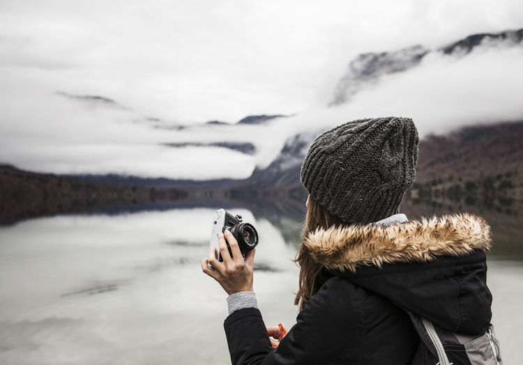 Winter Warm Clothing Photographing Activity Camera - Photographic Equipment Leisure Activity Photographer Outdoors Photography Themes Technology Cold Temperature Sky Hat Photographic Equipment Nature Camera Knit Hat Landscape Slovenia Lake Real People Girl