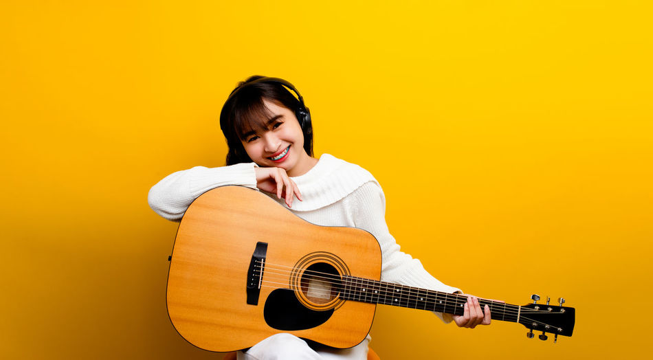 Young woman playing guitar against yellow wall