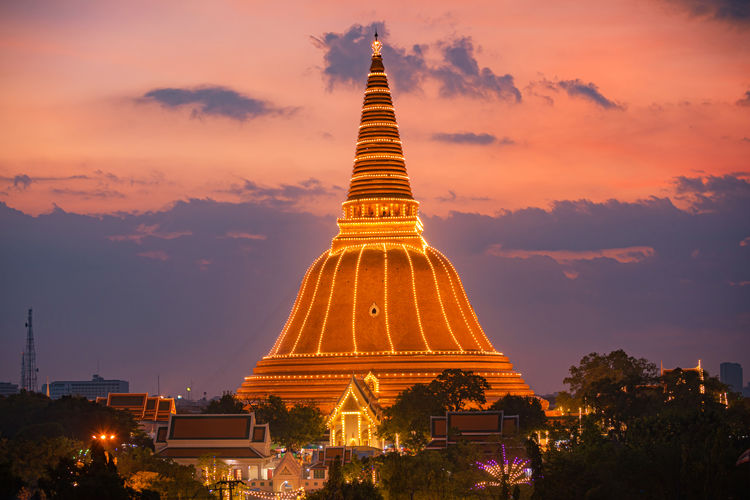 Illuminated temple building against sky during sunset