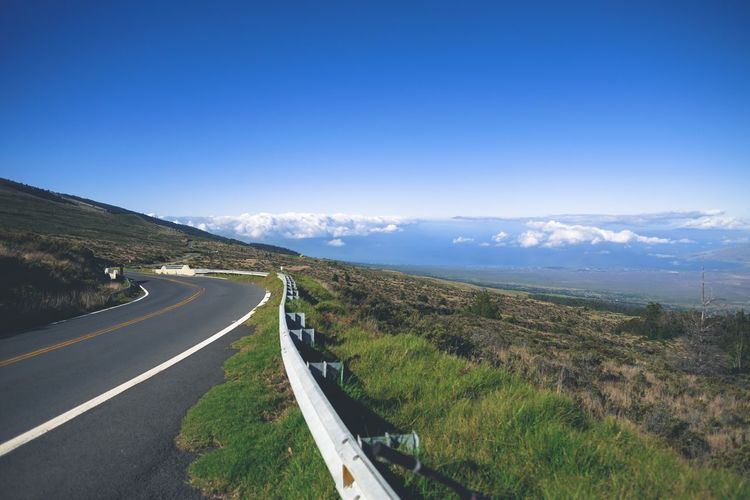 High angle view of road on mountain against blue sky