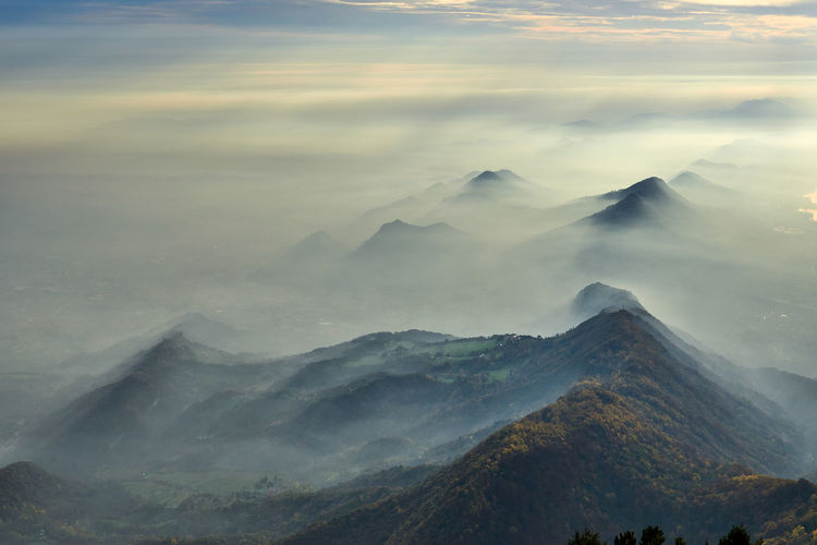 Scenic view of mountains with mist against sky