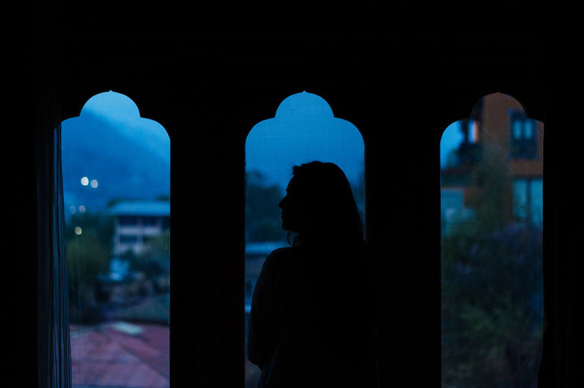 Woman looking out of the window early morning. Arch Architecture Built Structure Dark Focus On Foreground Illuminated Indoors  Leisure Activity Lifestyles Men Night One Person Real People Rear View Silhouette Standing Waist Up Window