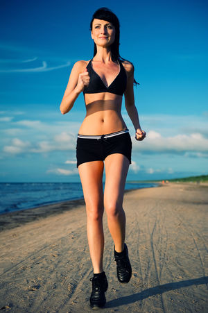 Woman running on the beach Cloud Running Slim Woman Beach Beautiful Woman Brunette Caucasian Jogger Jogging Leisure Activity Lifestyles Nature One Person Outdoors Real People Runner Sea Sky Sport Sportive Sportwear Women Young Adult Young Women
