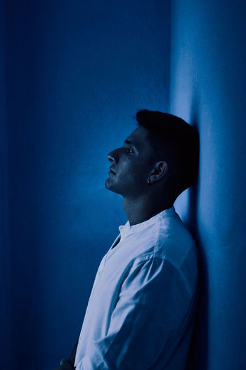 Side view of young man looking away against blue wall