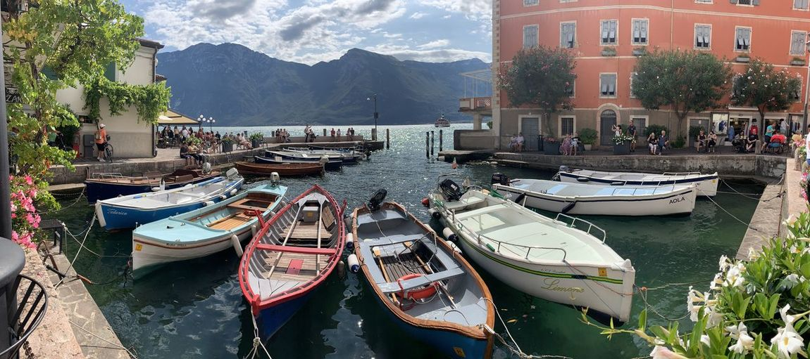 Panoramic view of boats moored in lake against buildings