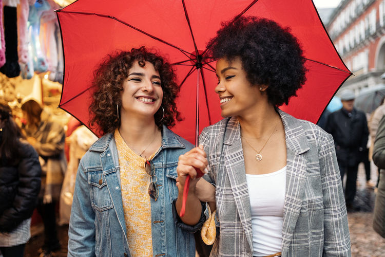 Happy young woman holding umbrella in city