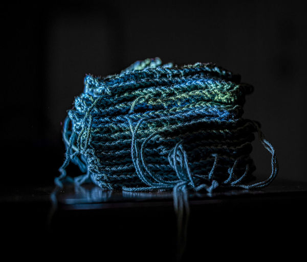 Close-up of rope on table against black background