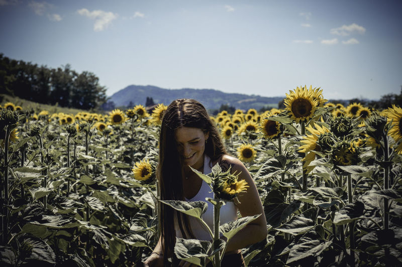 Woman standing at sunflower farm against sky